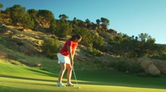 Golfer stroking golf ball into hole - stock footage