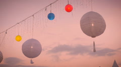 Slow motion of white and colored lamp lanterns blowing in the wind at sunset Stock Footage