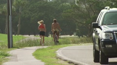 Man cycling and woman jogging on footpath Stock Footage