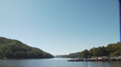 View of deck chairs and boats moored at Lake Lure Stock Footage