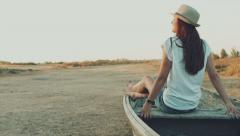 Beautiful girl with long hair sitting on an old tramp boat in the fields of dry Stock Footage