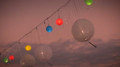 Red, yellow, green, blue, and white paper lanterns blow in the wind in slow mo Stock Footage
