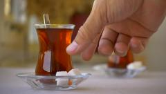 Sugar or sugar cubes may be added into tea glass. Slow Motion Stock Footage