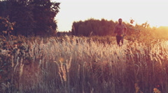 Young man is fast running on summer meadow - lovely sunset light Stock Footage
