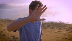 Man motions to camera to stop filming him at the beach Stock Footage