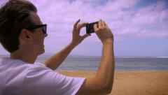 Handheld shot of tourist man on beach taking photos with his phone Stock Footage