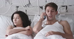 Young adult couple in the bed, boy on the phone Stock Footage