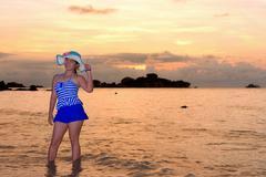Girl on the beach at sunrise over the sea - stock photo