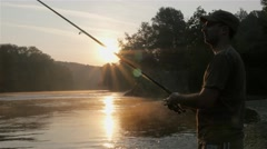 Fisherman fishing on river, casting hook, beautiful sunrise in background. 4k Stock Footage
