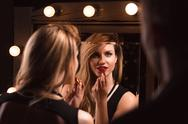 Stock Photo of Alluring woman applying red lipstick