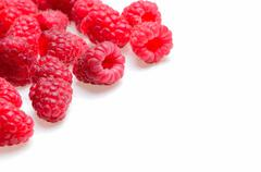 A scattering of raspberries on a white background Stock Photos