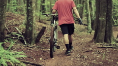 Young Man Walking Mountain Bike Uphill on Forest Trail.  Outdoor Sports Healt Stock Footage