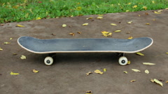 Skateboard by fall leaves on concrete Stock Footage