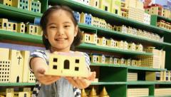Little Asian child showing wooden toy house Stock Footage