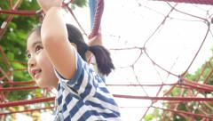Little Asian child climb on play equipment Stock Footage