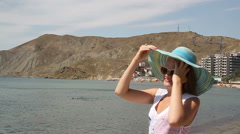 Young woman in a hat and glasses smiles on the background of the beach.. - stock footage