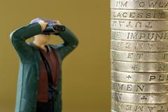 Single Miniature Model Looking at English Pound Coins - stock photo