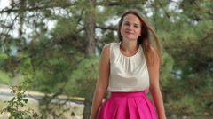 Young woman in a pink dress on the background of fir trees Stock Footage