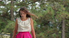 A pretty young woman standing against the backdrop of pine trees Stock Footage