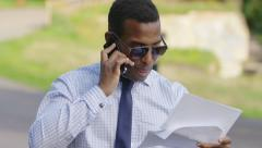 African american businessman quarreling using mobile phone: holding documents Stock Footage