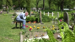 Sorrow man shrink near mother wife tomb in graveyard. 4K - stock footage