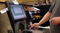 Man taking receipt after paying for food at self checkout counter Stock Footage