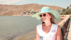 Young woman in sunglasses and hat smiling on the background of mountains Stock Footage