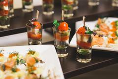 Catering for party. Close up of sandwiches, appetizers and fruit. Canapes - stock photo