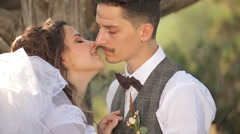 Bride and groom kissing on the background of a tree trunk - stock footage