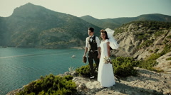 The bride and groom are standing on a cliff. Thirties. Vintage - stock footage