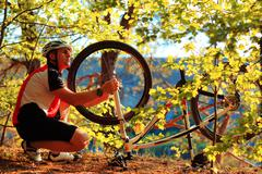 Man cyclist repairing a bike  in the wood - stock photo