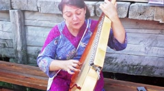 A woman sings and plays the bandura Stock Footage