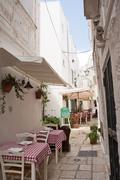 Table set in the alley of Cisternino (Apulia) Stock Photos