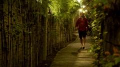Young man walking through narrow bamboo path at night HD Stock Footage