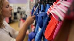 Female Choosing Flip-Flops in Sportswear Shoe Shop Stock Footage