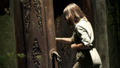 Young woman opening an old wooden door, at night Stock Footage