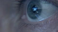 Closeup shot of man's eye surfing internet at night - stock footage