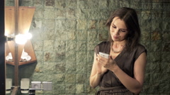 Young elegant woman using smartphone and checking her look in bathroom  HD Stock Footage