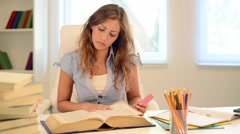 Tired teenage girl learning in the library. - stock footage