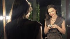 Happy, elegant woman using smartphone standing in front of mirror in bathroom HD Stock Footage