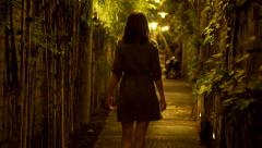 Young woman walking through narrow bamboo path at night HD Stock Footage