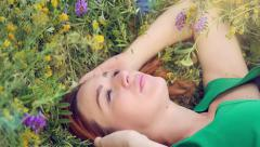 pensive dreamy attractive young red-haired woman with flowers relaxing outside - stock footage