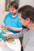two men doing a crochet course - stock photo