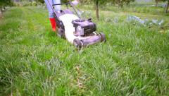 Person using lawn mower in a orchard Stock Footage