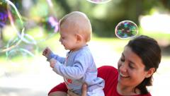 Cute baby catching soap bubbles in a summer day Stock Footage