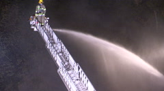 Firefighters pour water on smoky plaza fire at night in Waterloo. Stock Footage