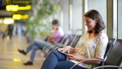 Young woman using a digital tablet in airport waiting area Stock Footage