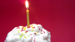 Cupcake with a lit candle over red background - stock footage
