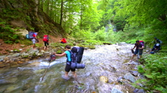 Mountaineers crossing the river barefoot in a summer day Stock Footage