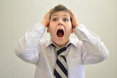 Teen boy screaming holding his hands behind  head - stock photo